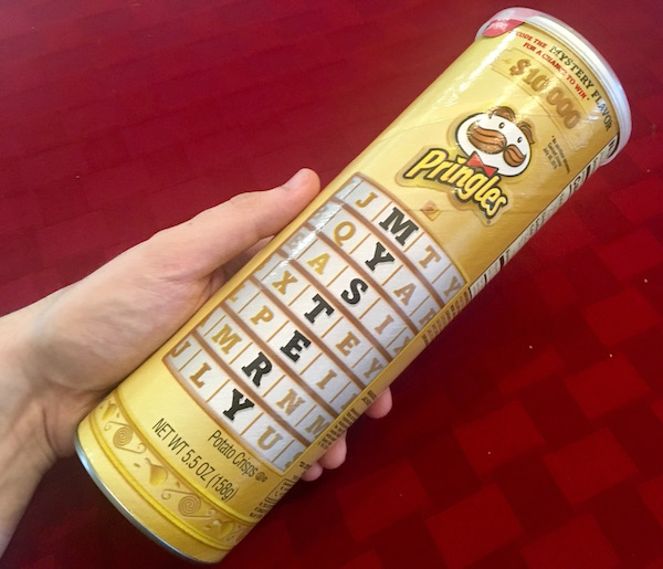 "The gold Mystery Flavor Pringles tube with a cryptex-like graphic that reads ""MYSTERY."""