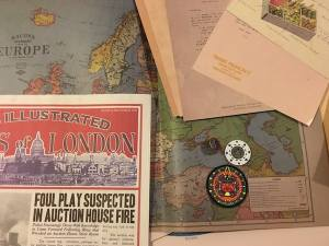 A newspaper, a map, a poker chip, an a patch with a South American-esque design.