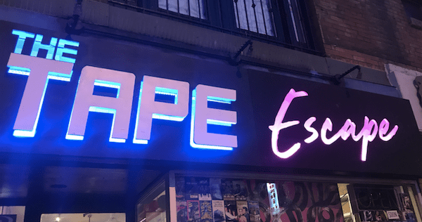 Tape Escape exterior - a video store with the event logo.