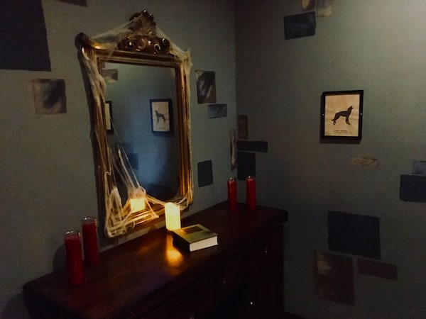 In-game: a spooky mirror flanked candles above a dresser.