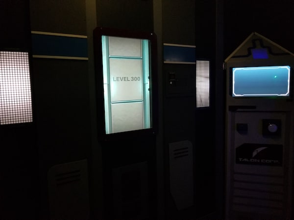 "In-game: A futuristic elevator with a doorway labeled ""Level 1"""