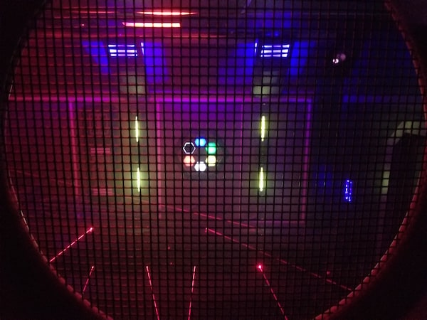 In-game: A hexagon made from multicolored glowing hexagons surrounded by lasers.