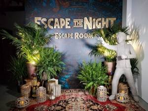 "The photo wall, decorated with plants, props, and an ""Escape the NIght Escape Room"" sign."