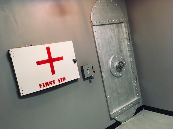 """In-game: A plain, silver walled room, with an interesting riveted door and a large white panel labeled """"First Aid"""""""