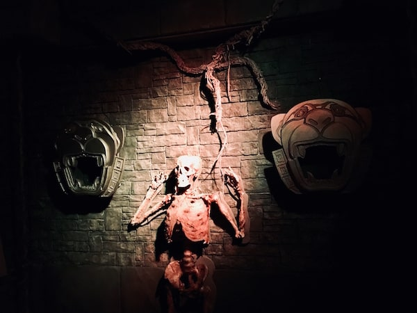 In-game: A human skeleton hanging from a wall between two panther sculptures.
