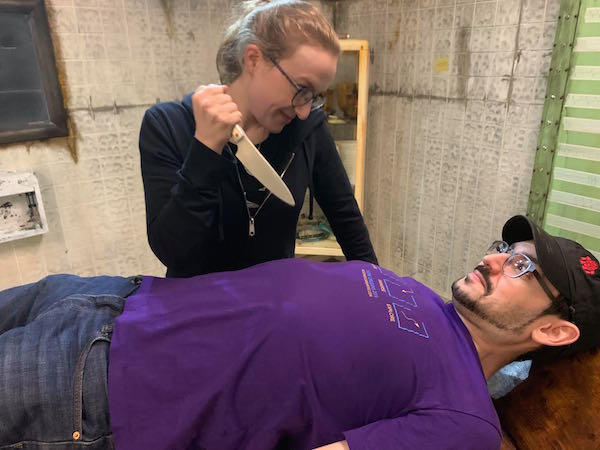 Post-game: David laying on an operating table, list looking into his eyes with a knife in her hand.
