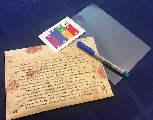 In-game: an introductory letter on a sealed envelope, a piece of acetate, a dry erase marker, and a small piece of cardboard with 5 different size/color bars on it.