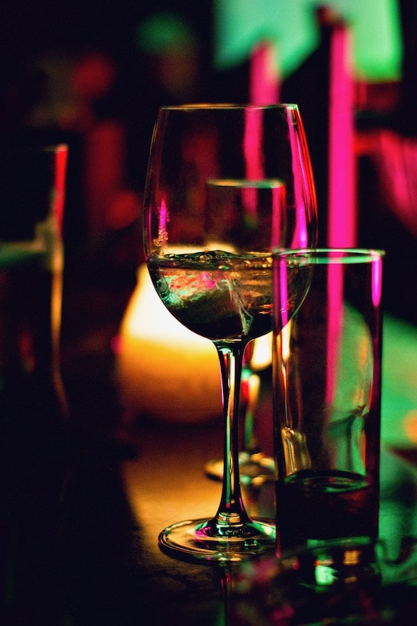 A partially consumed glass of wine beside a mostly consumed glass.