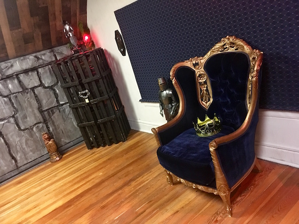 In-game: a large throne with a crown sitting on the seat.
