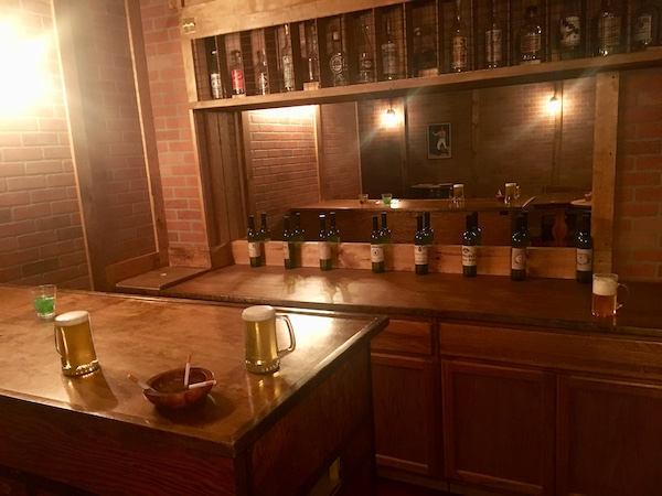 In-game: A bar with beers, a mixed drink, and an ashtray laying atop it.