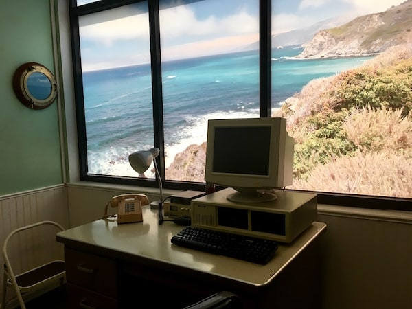 In-game: An old Tandy computre in front of a large window with a ocean view.