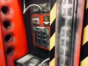 In-game: closeup of containment technology, there are buttons and knobs.
