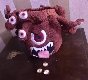A stuffed Beholder on a table.
