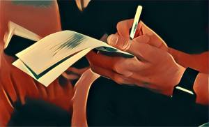 Hands writing a note on a notepad.