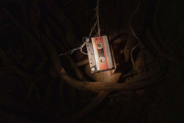 Light shines on a cassette tape dangling from a piece of twine in front of a background of tree roots.
