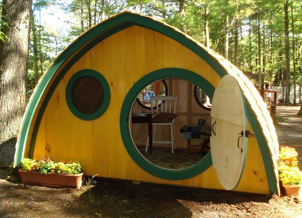 A Hobbit Hole home open with small furniture inside.