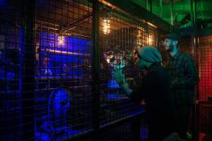 In-game: Two people looking into a caged area and some strange artifacts.