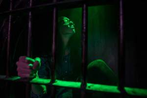 In-game: A person in a cage bathed in green light grasping one of the bars.