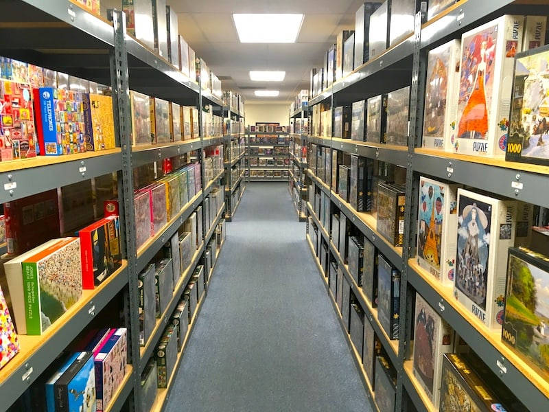 A very long aisle filled with jigsaw puzzle boxes.