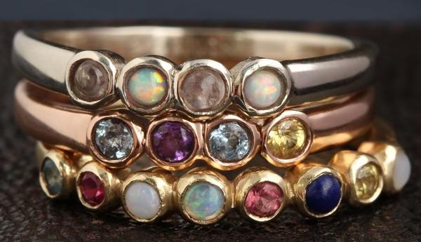 A stack of three rings in silver, gold, and rose gold. Each has a different arrangement of stones on the band.