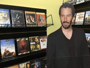 In-game: a cardboard cutout of Keanu Reeves beside a shelf of DVDs.
