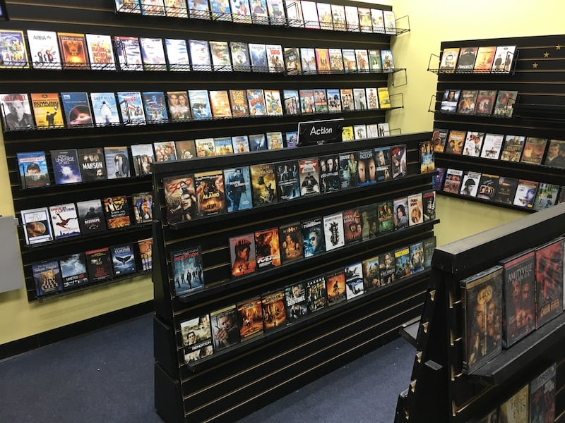 In-game: Wide view of a video store with shelves of DVDs.