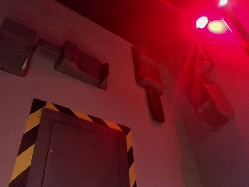 In-game: An assortment of wallmounted machinery and a flashing red alarm light.