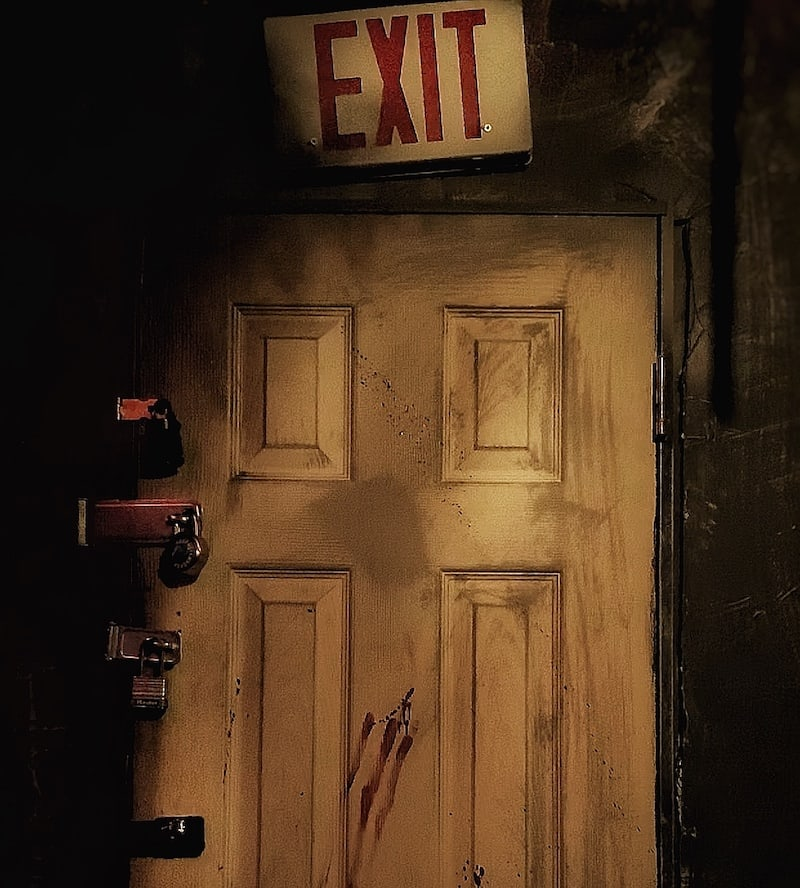 In-game: A door covered in padlocks with an exit sign above it.