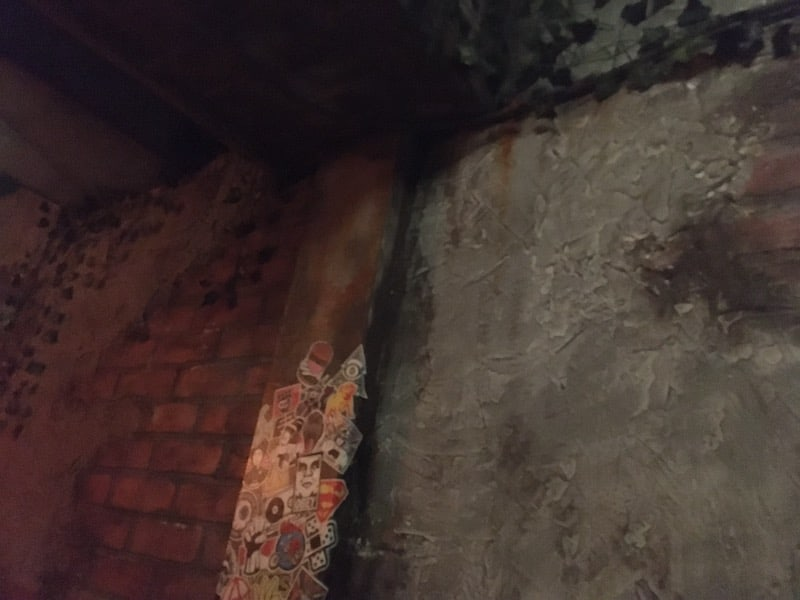 In-game: A detailed, heavily worn brick, concrete, and steel wall.