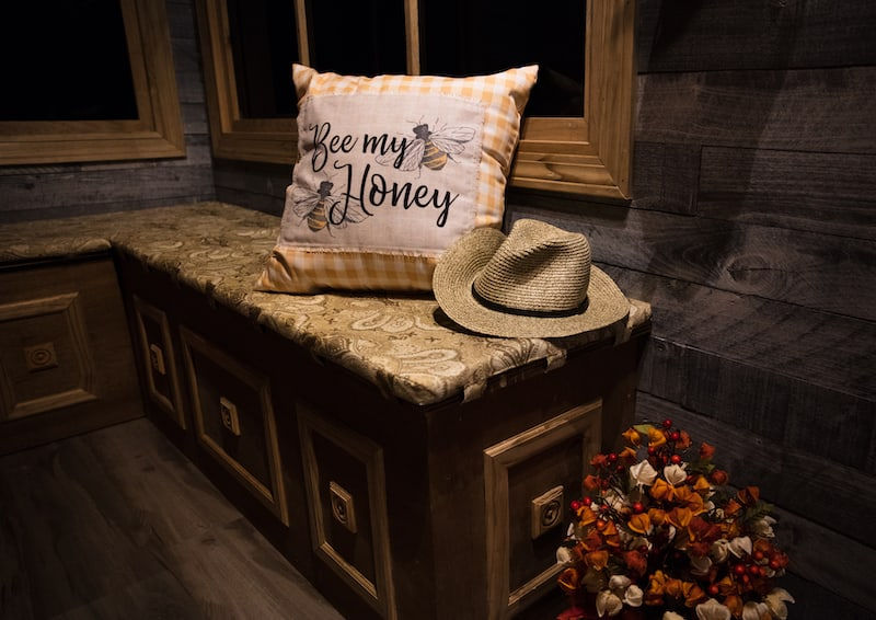 """In-game: A corner bench seat with a pillow that reads, """"Bee my honey"""" depicting two bees."""