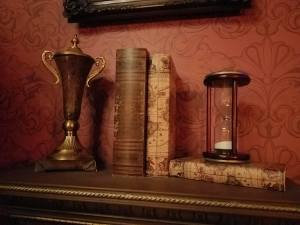 A trophy, an hourglass, and some books sit on an ornate shelf.