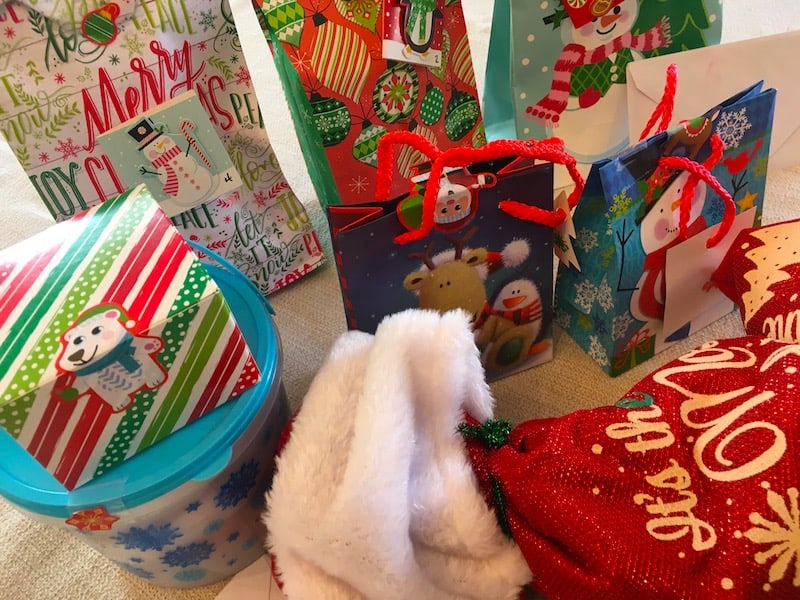 An assortment of bagged and wrapped christmas gifts.