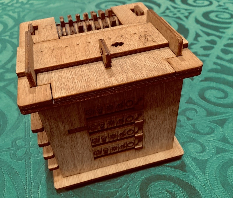 Back of the wood puzzle box with a series of icons engraved into the side with sliders.