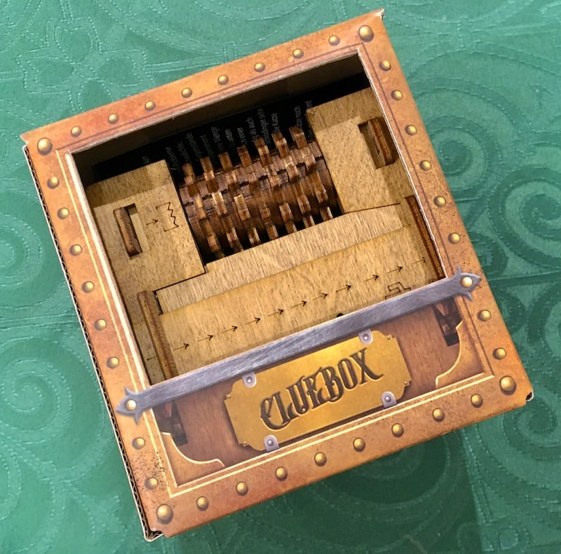 """A wooden puzzle box inside of its cardboard packaging labeled, """"Cluebox."""""""