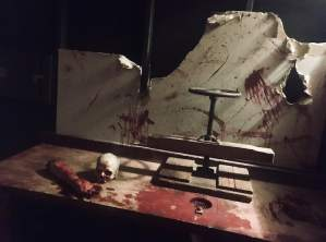 In-game: A table covered in blood, body parts, and a large clamp.