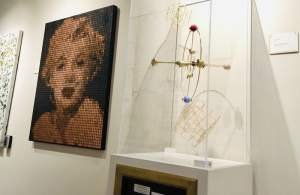 In-game: A portrait of Marilyn Monroe made out of pennies beside a geometic sculputre.