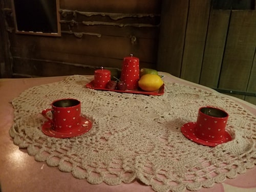 Teacups, candles, and fruit on a doily-covered table.
