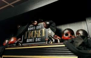 "In-game: an ""Admit One Ticket"" sign flanked by freaky baby doll parts pained black and red."