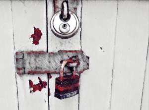 An old rusty master lock and a disk lock securing a door.