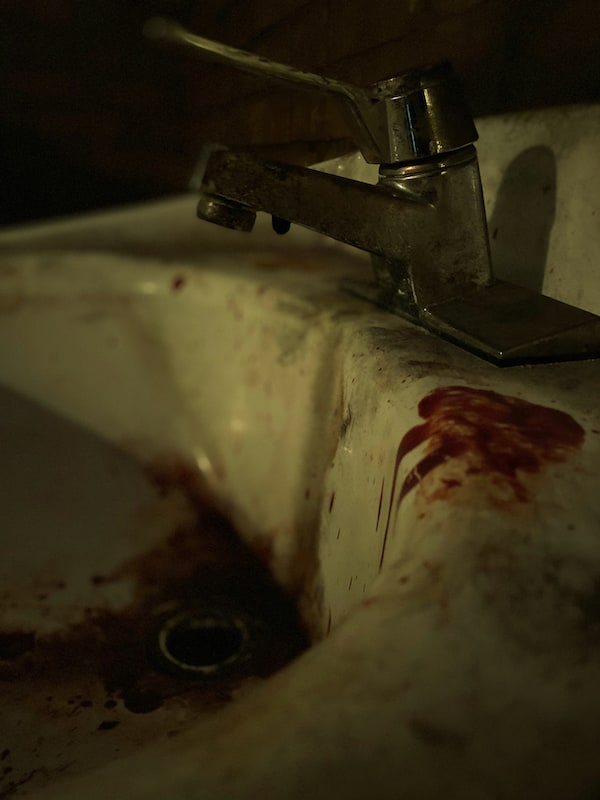 A dirty sink splattered with blood.