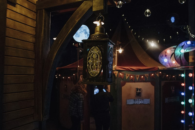 In-game: The citcus exterior with a large tent illuminated in the moonlight.