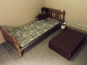 In-game: A ratty bed with a large stuffed animal on it. Beside the bed on the floor is a massive briefcase.