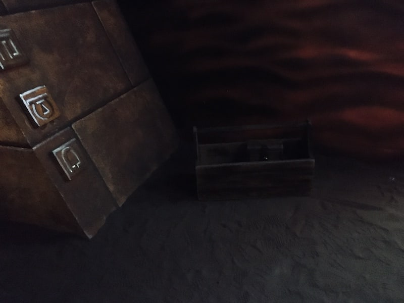 In-game: A wooden toolbox sitting in the sand beside the base of an ancient pyramid.