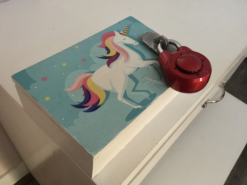 In-game: Closeup of a box with a unicorn painted on it, sealed with a red directional lock.
