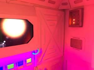 In-game: A spaceship's interior, through the window a sun burns bright.