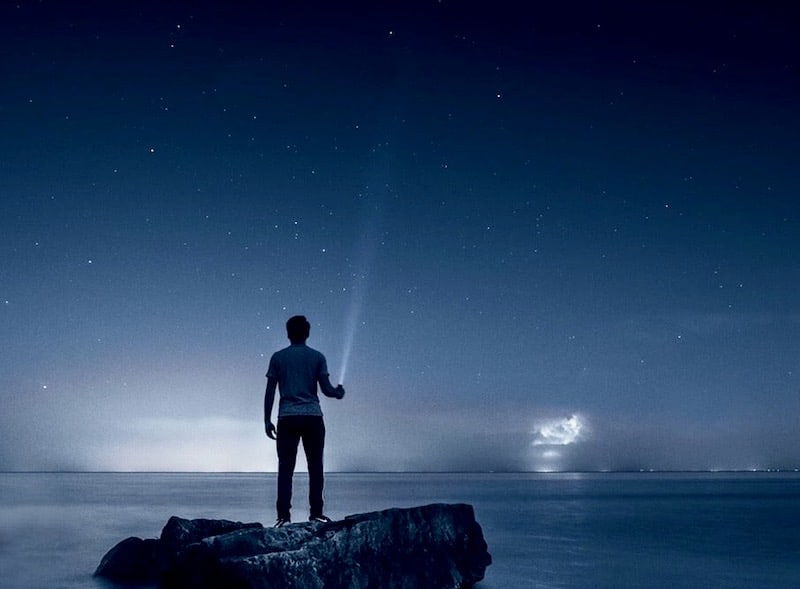 A lone person standing on a island in the middle of the water holding a flighlight in the darkness.