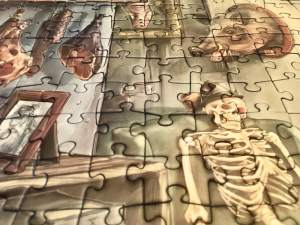 Portion of the puzzle - a closeup of a human skeleton with red glowing eyes and a fedora.