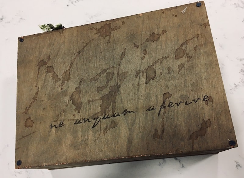 An old wooden box with latin enscribed on its face.