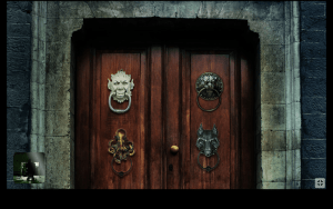 A door with 4 different knockers on it. A demon, a lion, a wolf, and an octopus.