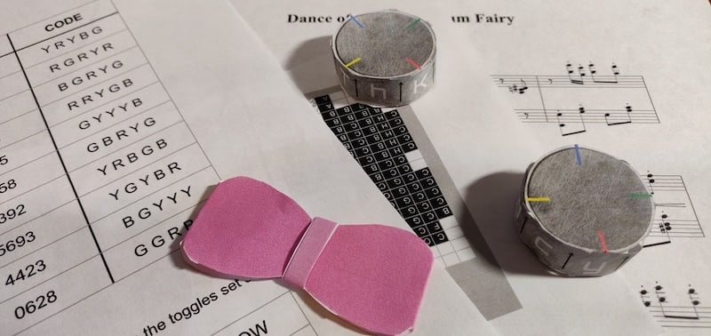 A collections of papers, cipher dials, and a pink paper bowtie.